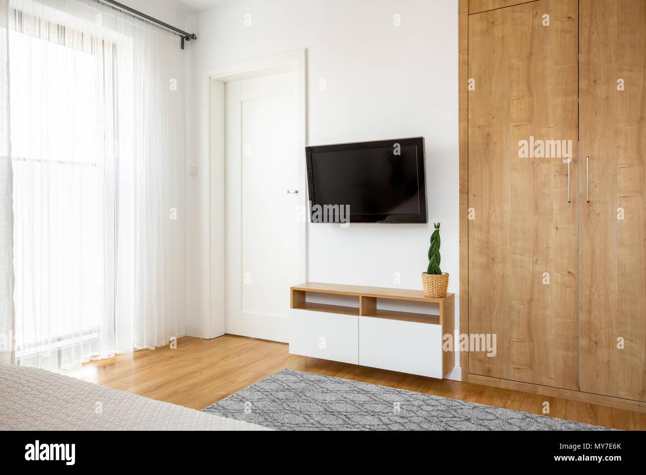 Armoire En Bois A Cote De La Television Sur Le Mur Blanc