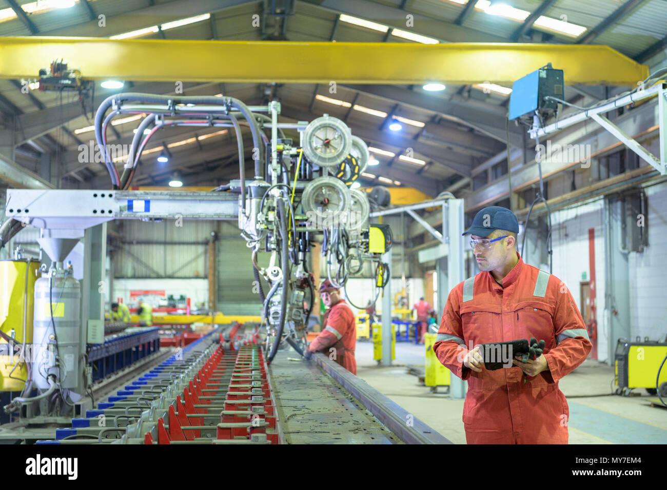 Avec l'inspecteur d'exploitation des travailleurs dans la machine de soudage par faisceau d'usine de remorque Photo Stock