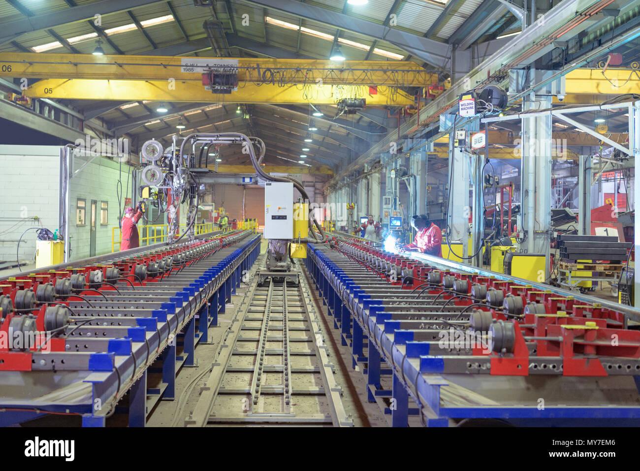 Vue grand angle avec des travailleurs dans la machine de soudage par faisceau d'usine de remorque Photo Stock