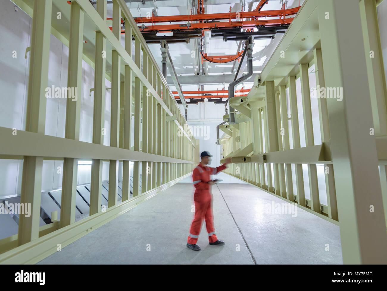 L'inspection du châssis peint travailleur en salle de séchage à l'usine de remorque Photo Stock