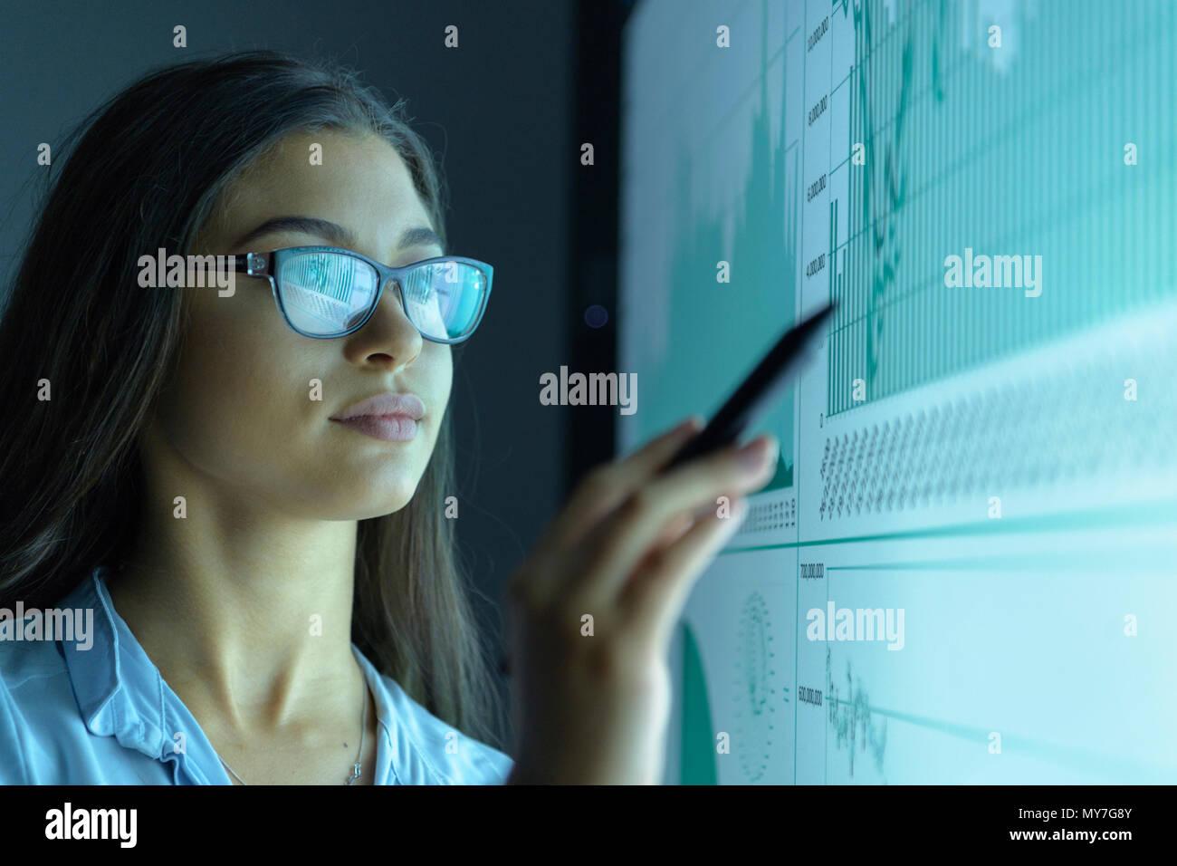 Businesswoman étudier les graphiques sur un écran interactif en réunion d'affaires Photo Stock