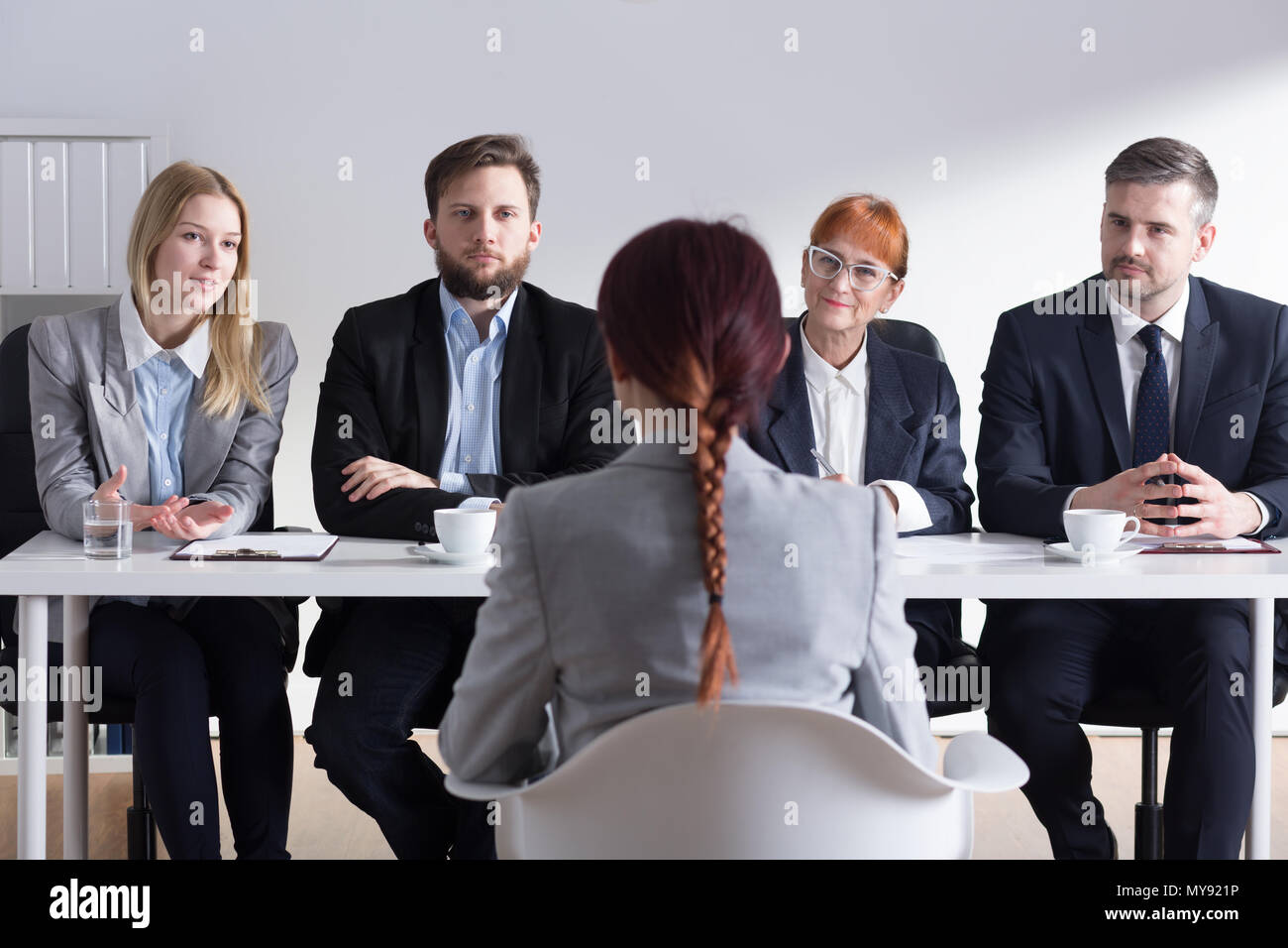 Femme lors d'entrevue d'emploi et quatre businesspeople sitting par table office Photo Stock