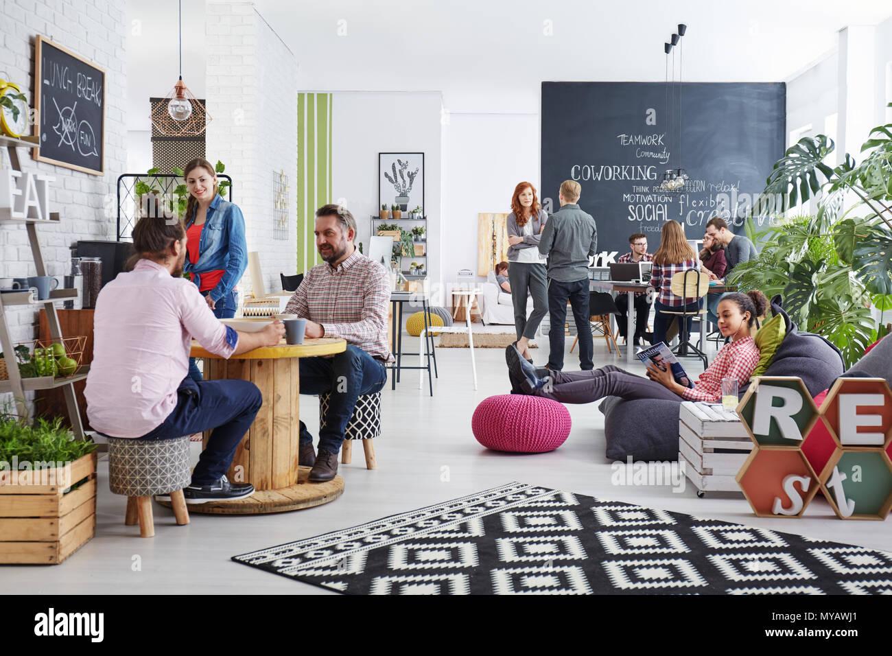 Les personnes travaillant dans l'agence moderne au cours du déjeuner relaxant Photo Stock