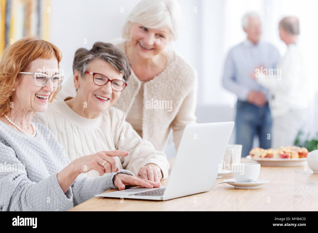 Trois femmes plus âgées ayant recours à l'ordinateur portable pour regarder des photos Banque D'Images