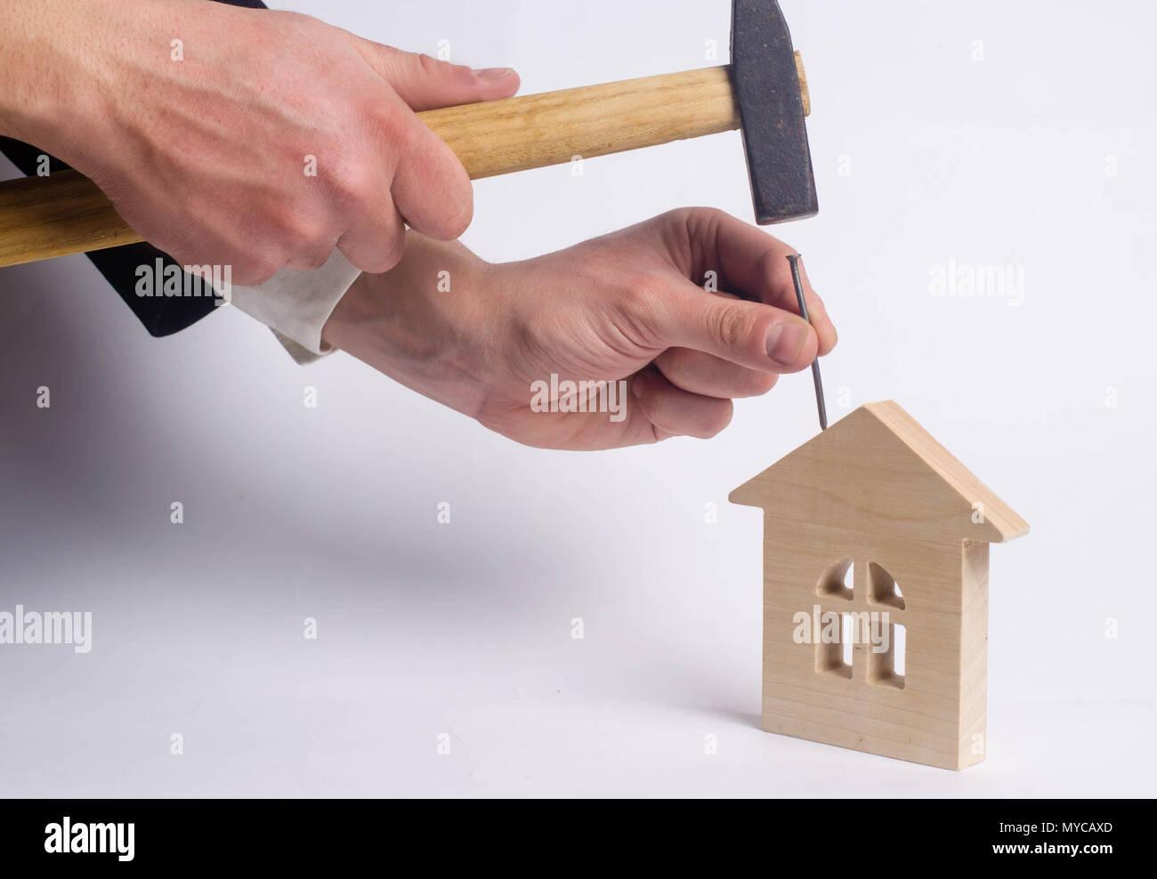 Marteaux homme un clou avec un marteau dans une maison en bois miniature sur un fond blanc. Concept de la réparation des maisons. Le travailleur effectue des travaux de réparation dans th Banque D'Images