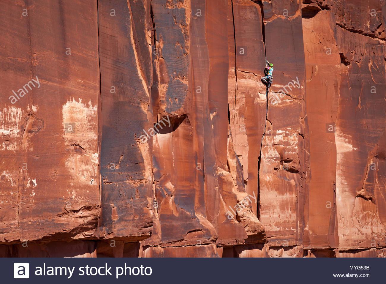 Un male rock climber en vêtements colorés monte une fissure grimper connu comme Chasin jupe en midi. Photo Stock