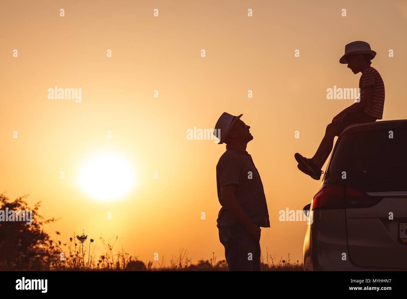 Père et fils jouer dans le parc à l'heure de coucher du soleil. Les gens s'amusant sur le terrain. Concept de famille accueillante et des vacances d'été. Photo Stock
