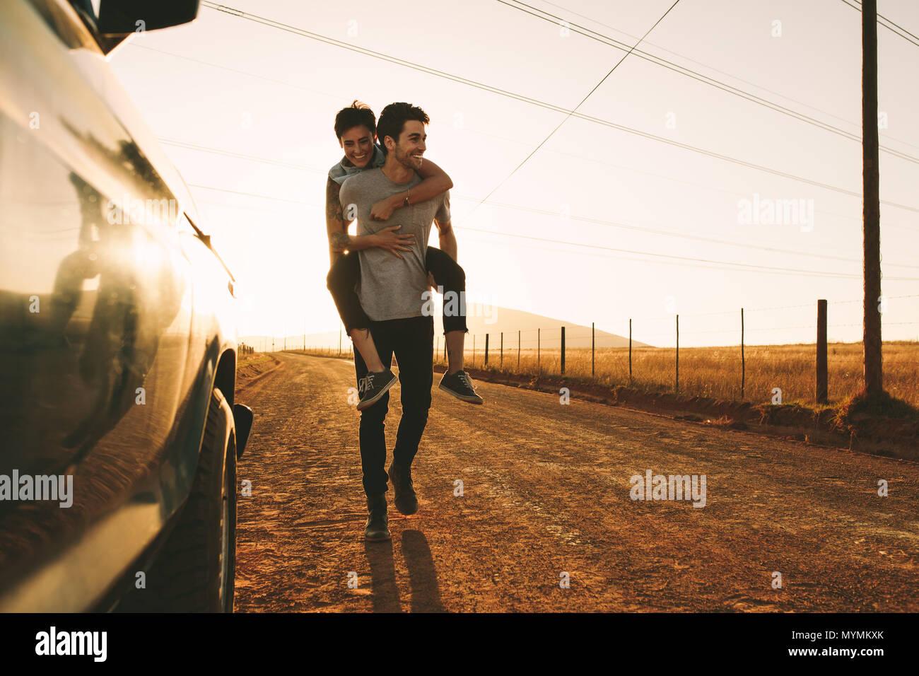 Woman piggy à cheval sur un homme à l'extérieur dans la campagne. Homme portant une femme sur son dos tandis que sur un voyage sur la route. Photo Stock