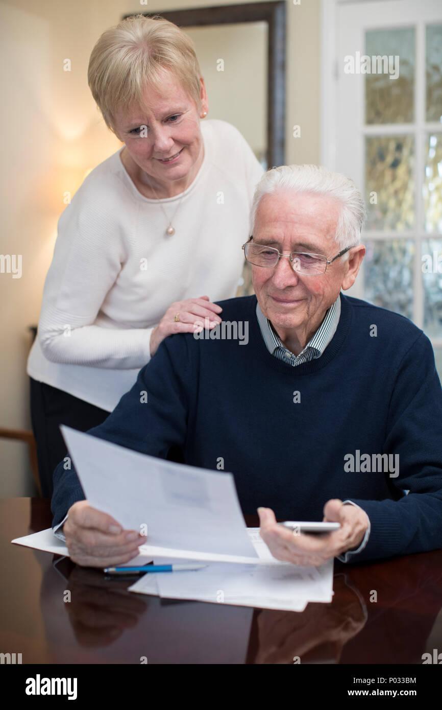 Happy Senior Couple d'examiner ensemble les finances nationales Photo Stock