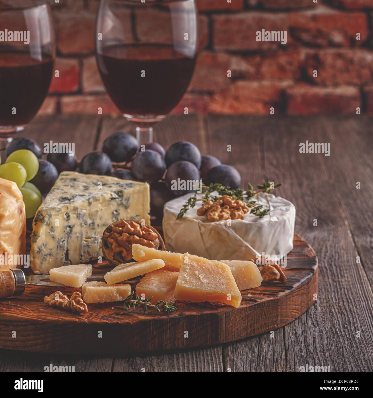 Le fromage, les noix, les raisins et le vin rouge sur fond de bois, selective focus. Photo Stock