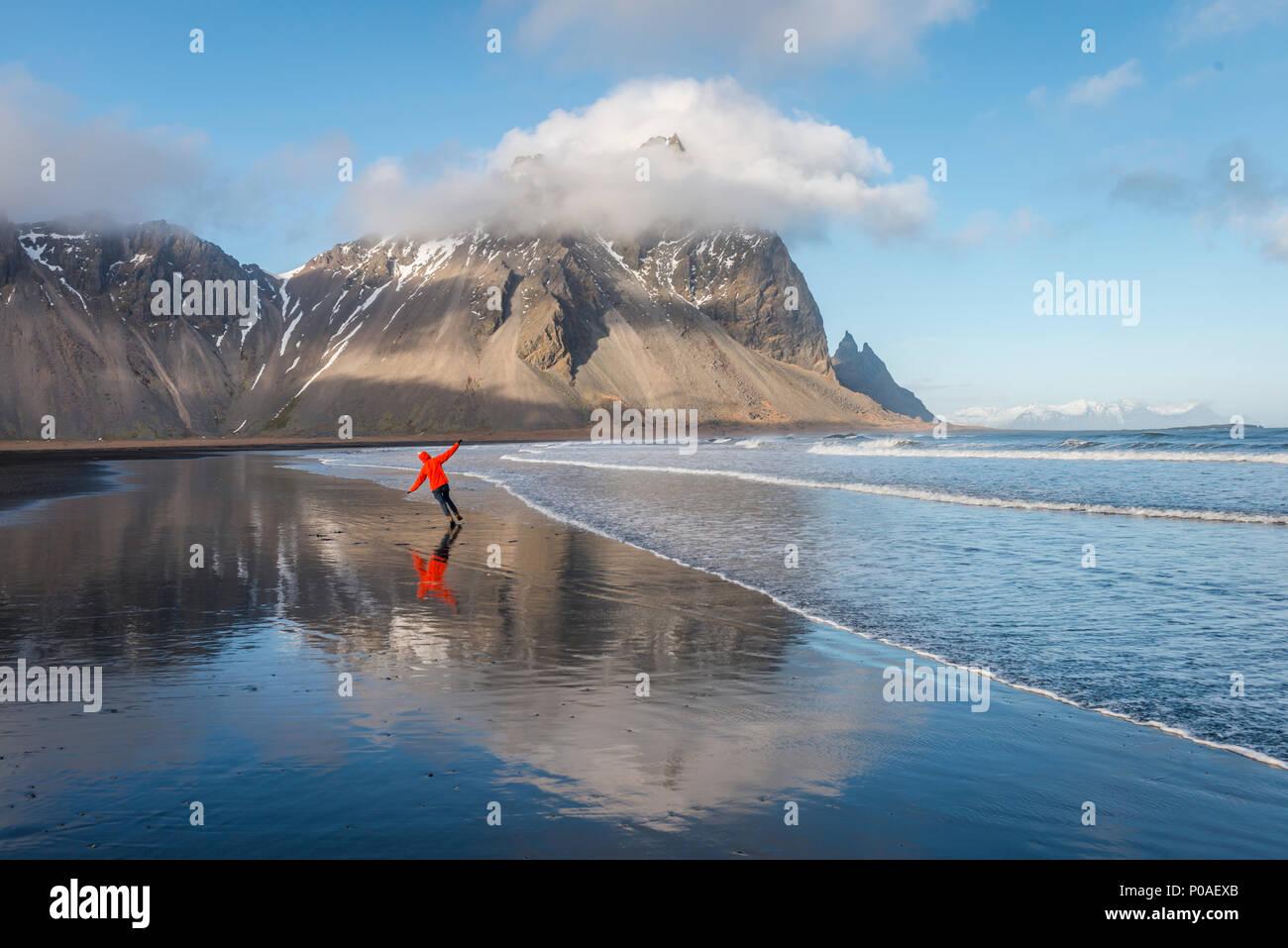 L'homme s'exécute dans la bonne humeur sur une plage de sable noir, montagnes, Klifatindur Kambhorn Eystrahorn, pointe Stokksnes et Photo Stock