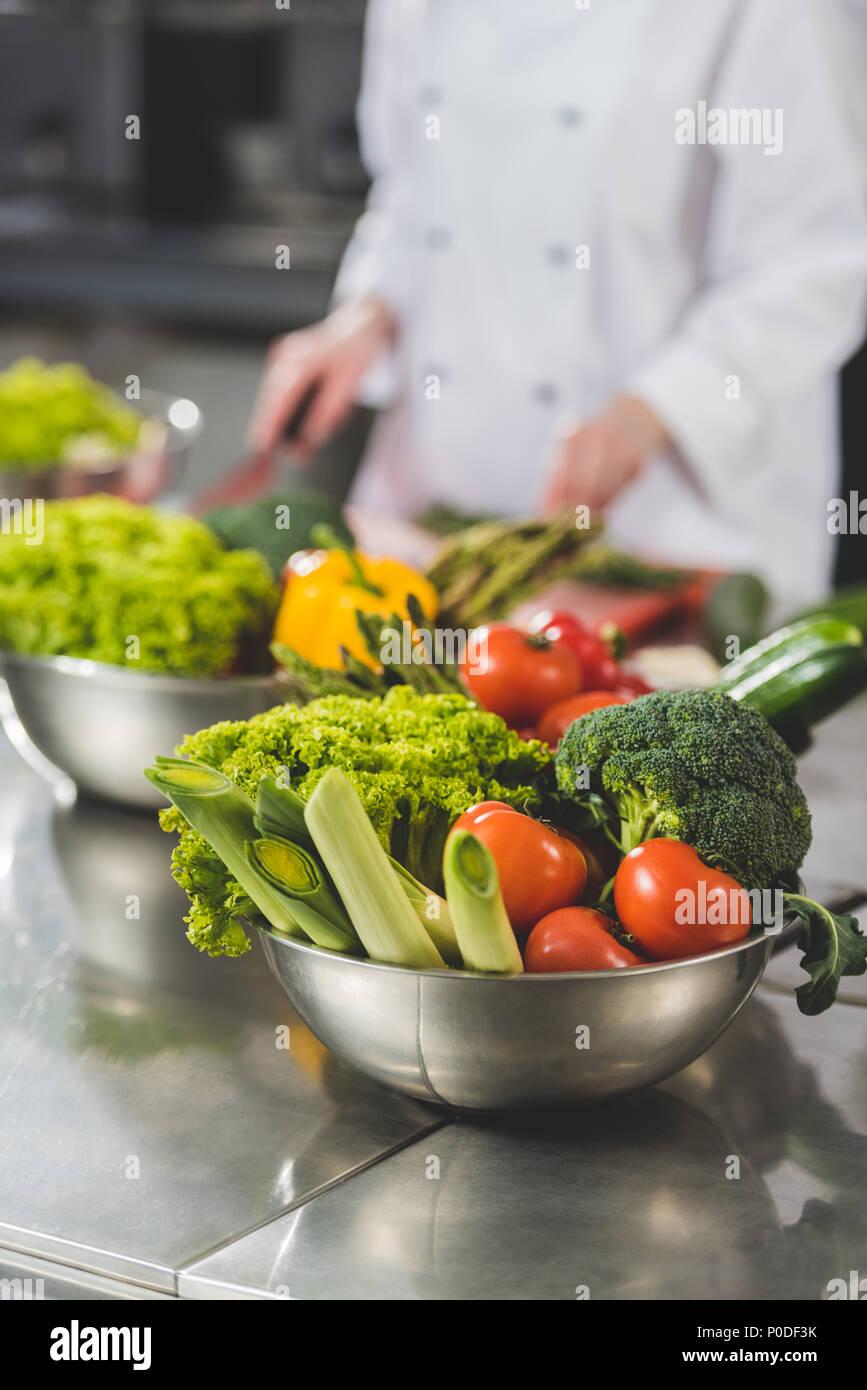 Portrait de chef de cuisine dans une cuisine de restaurant avec des légumes sur le premier plan Photo Stock