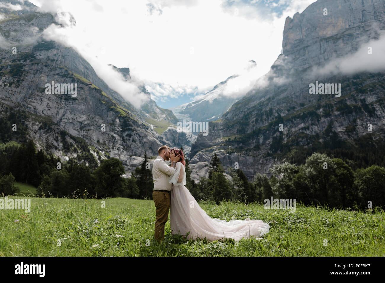 Happy Bride and Groom hugging et embrassant sur la montagne verte prairie avec nuages dans Alpes Photo Stock