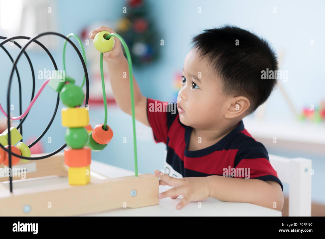 Tout-petits Asie adorable baby boy sitting on chair et en jouant avec des jouets de couleur à la maison. Photo Stock