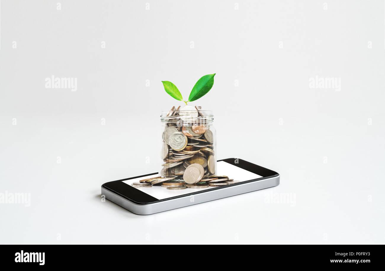 Services bancaires en ligne et faire de l'argent par les affaires en ligne et e-commerce. Téléphone mobile et de verre pot plein de pièces Photo Stock