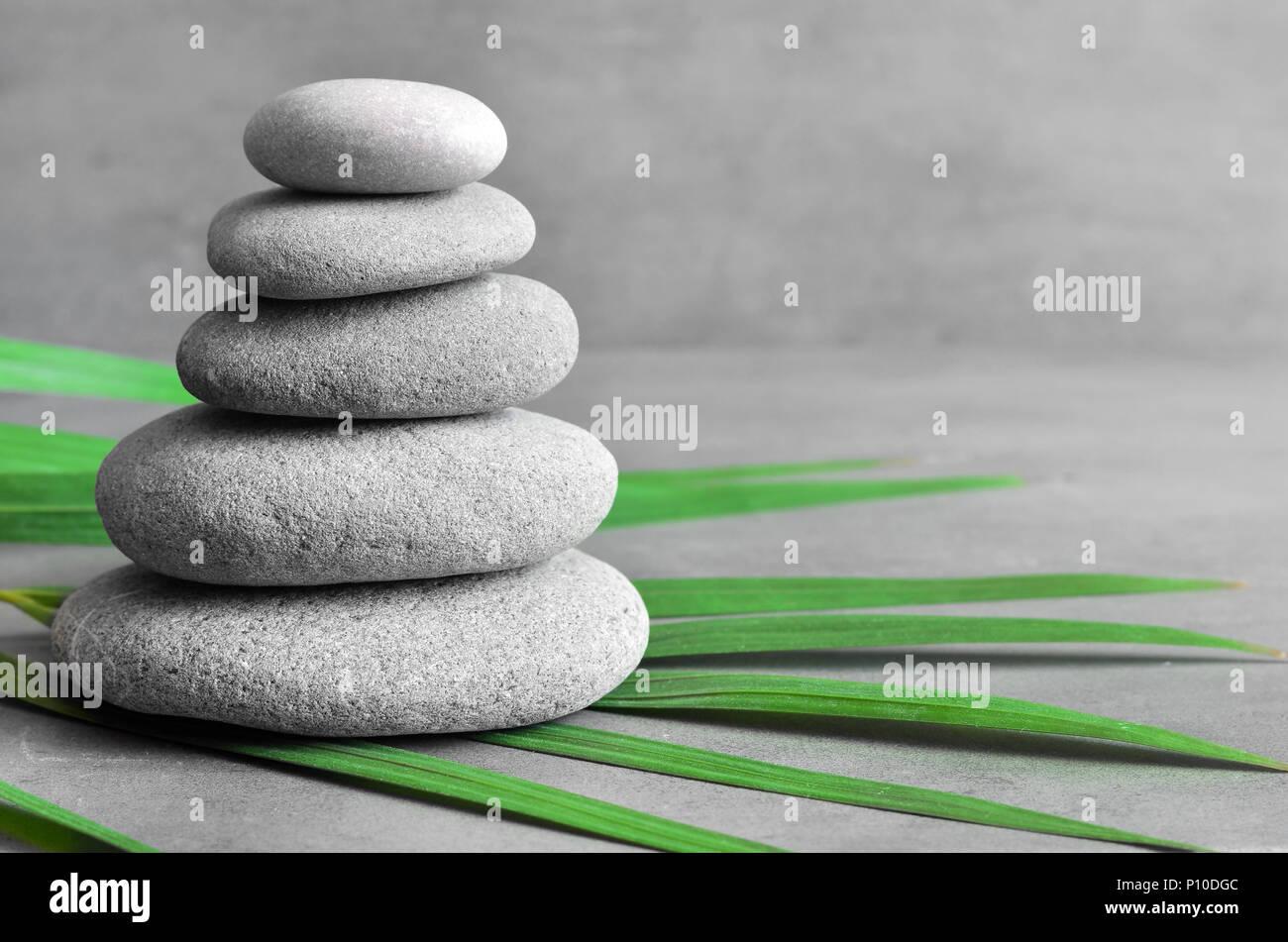 L'équilibre des pierres et le vert feuille de palmier. Concept spa et zen. Photo Stock