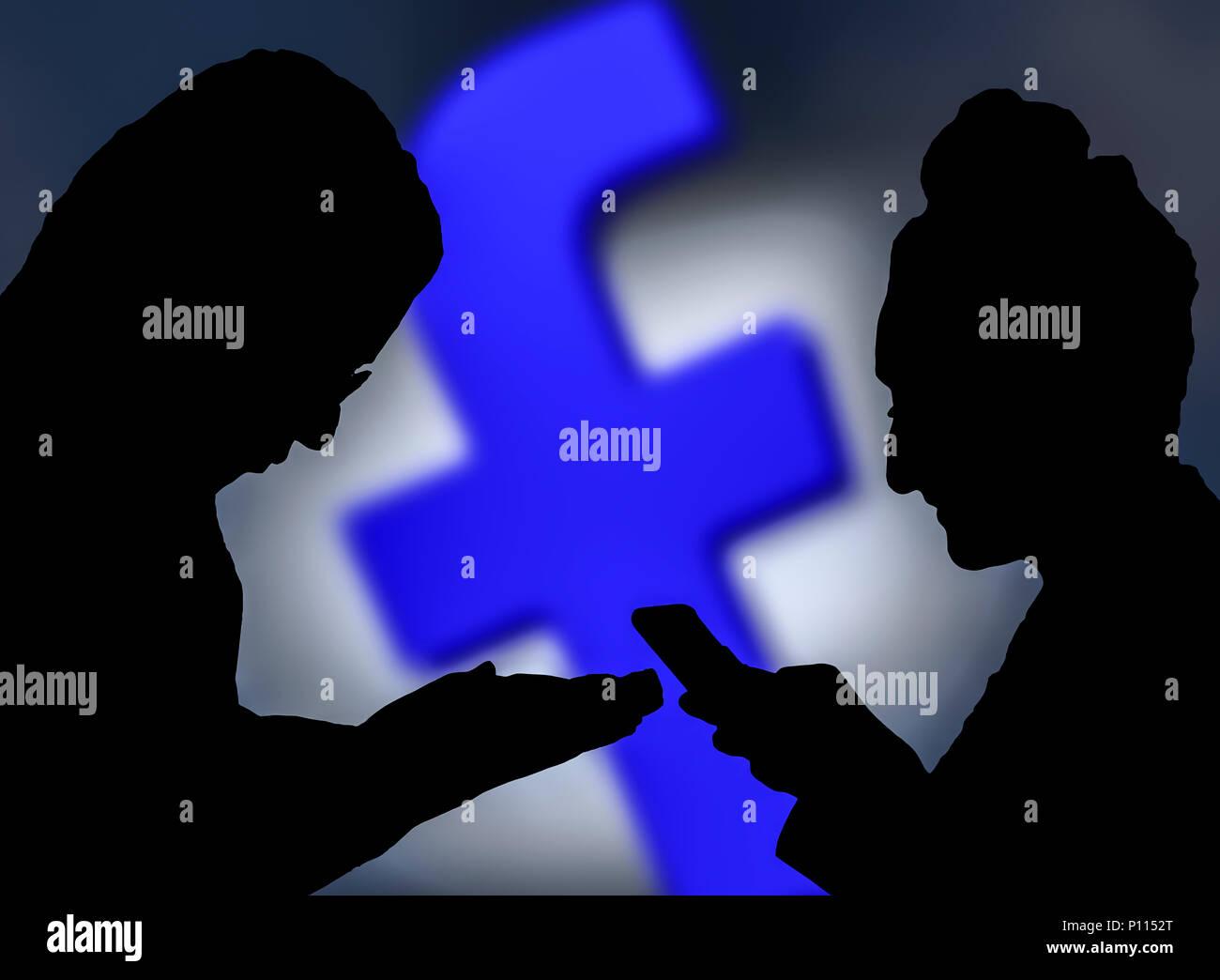 Silhouettes d'un couple de personnes utilisant l'application Facebook sur les smartphones. 2 personnes sur le chat et rencontre sur Facebook. Photo Stock
