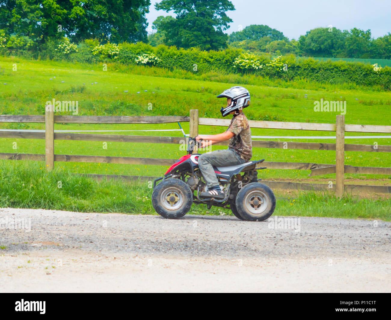 Jeune Garçon Portant Un Casque De Sécurité équitation Un Petit Quad