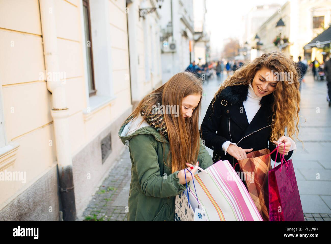 Deux jeunes femmes est satisfait de shopping et marche dans la rue Photo Stock