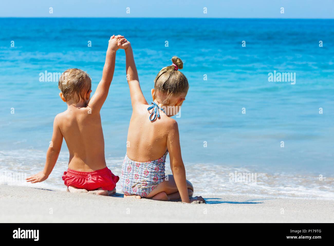 Happy kids ont in surf sur la mer plage de sable fin. Les enfants sont assis dans l'eau avec les mains. Style de voyage, vacances en famille activités natation Photo Stock
