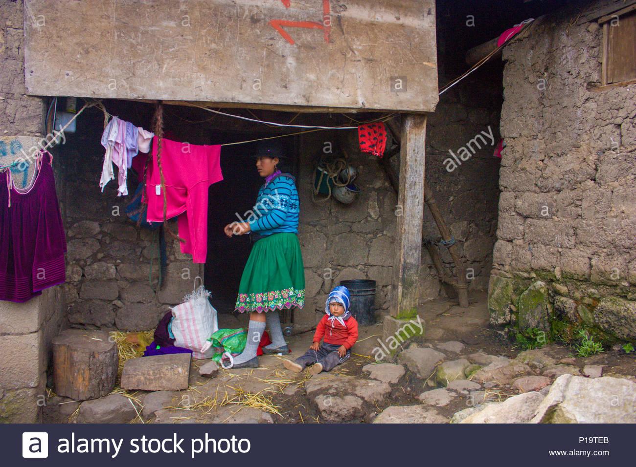 Femme et enfant en costume traditionnel. Vie quotidienne de la population équatorienne dans la cordillère des Andes. Ils vivent dans une maison de la pierre avec de la terre Photo Stock