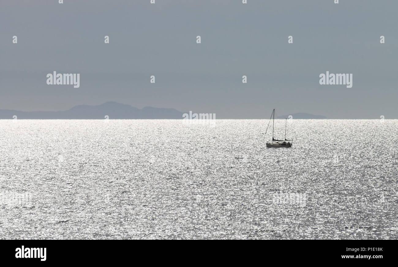 Image paysage d'un yacht sur l'océan de l'eau avec la terre à l'horizon contre un ciel bleu clair avec copie espace Photo Stock