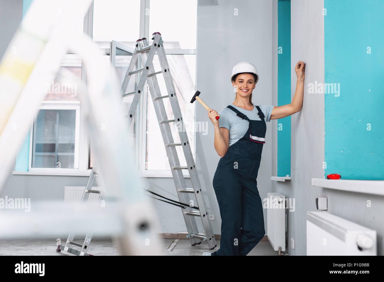 Femmes gaies builder holding a hammer Banque D'Images
