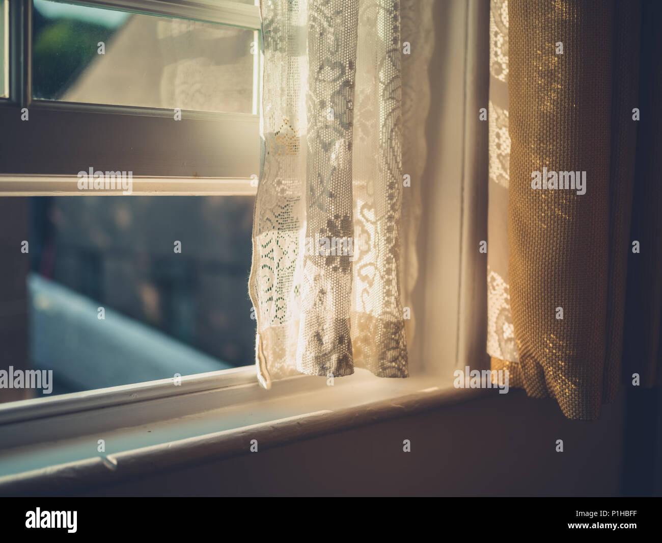 Après-midi du soleil frappant un rideau à travers la fenêtre Photo Stock