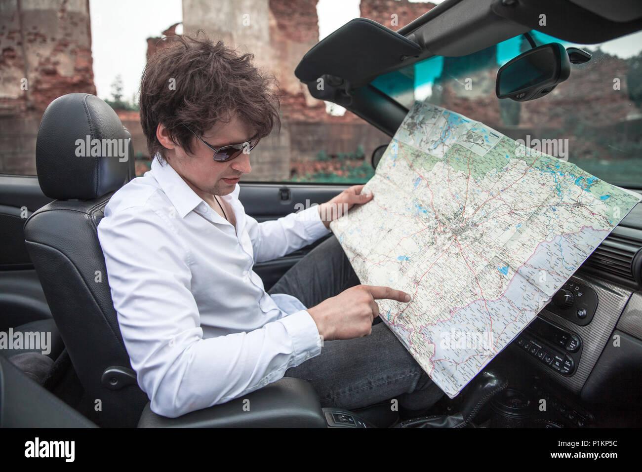 Beau jeune homme est titulaire d'une carte de route dans une voiture. Voyages et aventures concept. Tonique photo Banque D'Images