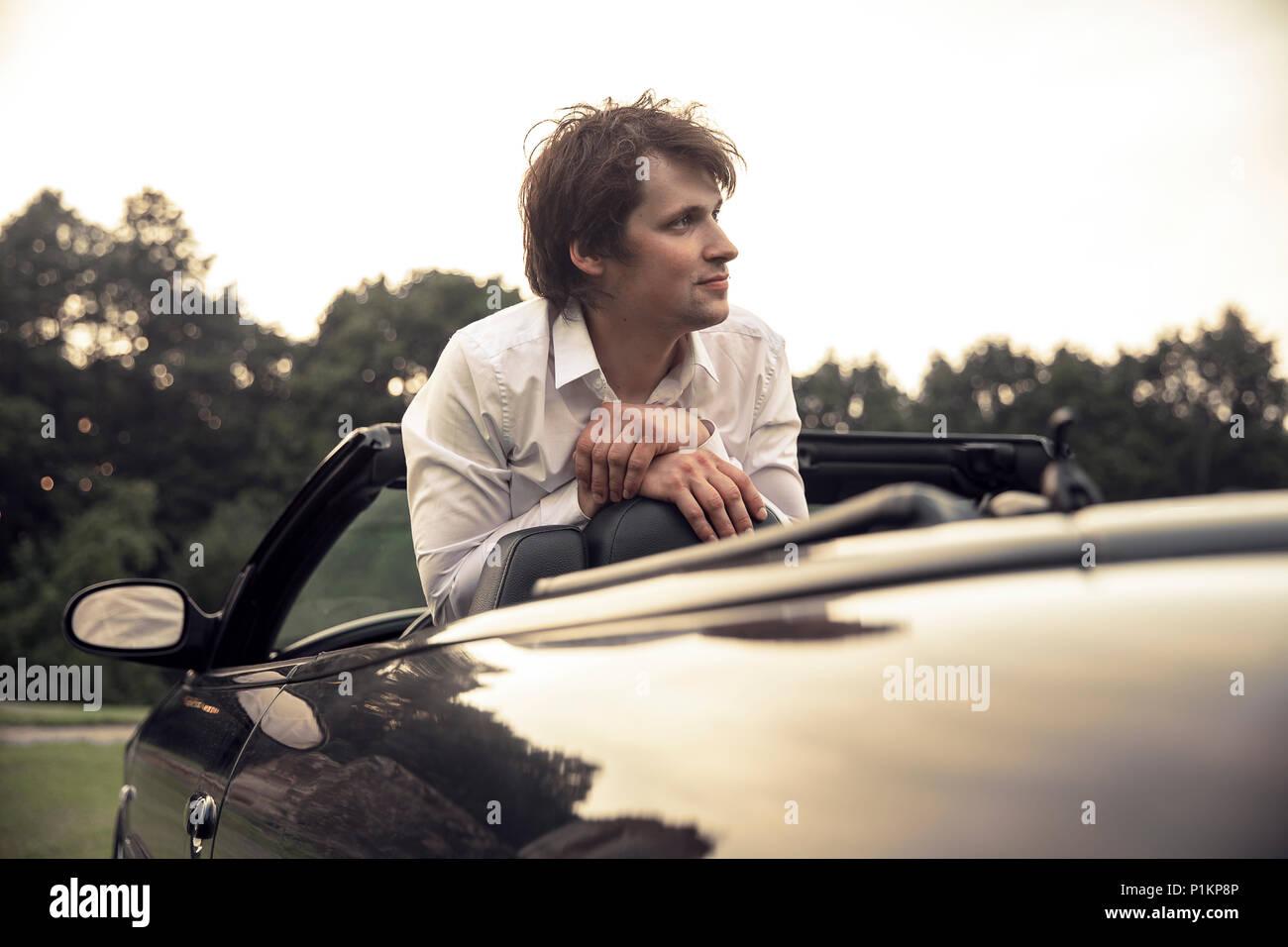 Beau jeune homme assis dans une voiture. Voyages et aventures concept. Tonique photo Banque D'Images