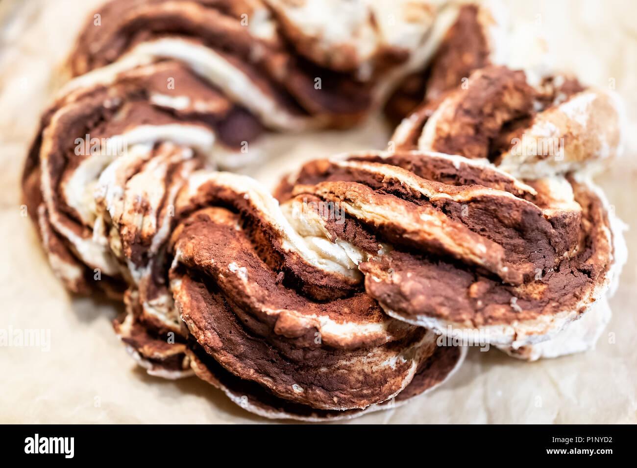 Gros plan du tressé rouge doré au four à la cannelle orange toute torsion swirl pain gâteau en spirale sur le papier parchemin bac pour des vacances festives Photo Stock
