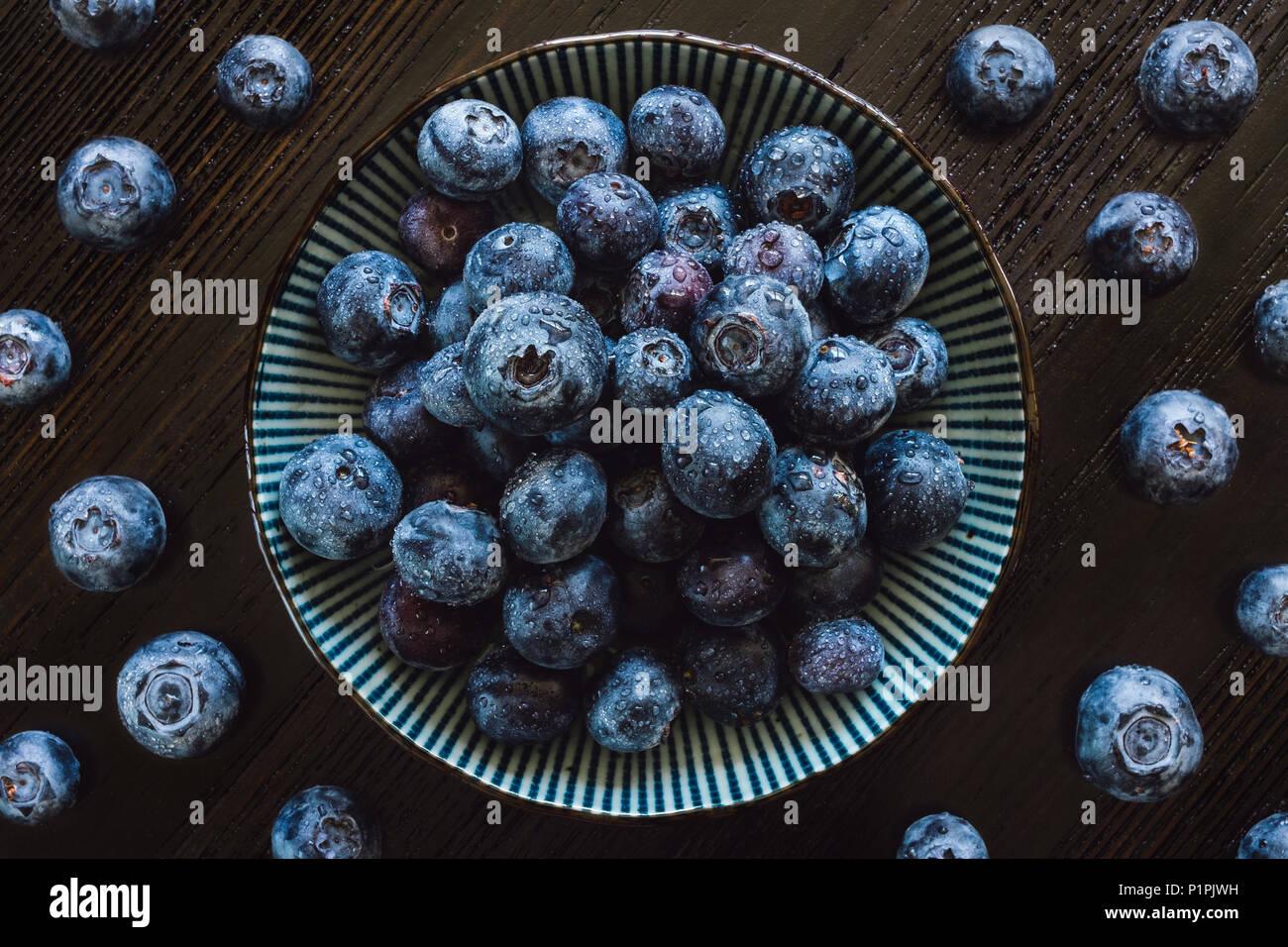 Bleuets frais dans un bol et sur table en bois sombre. Photo Stock