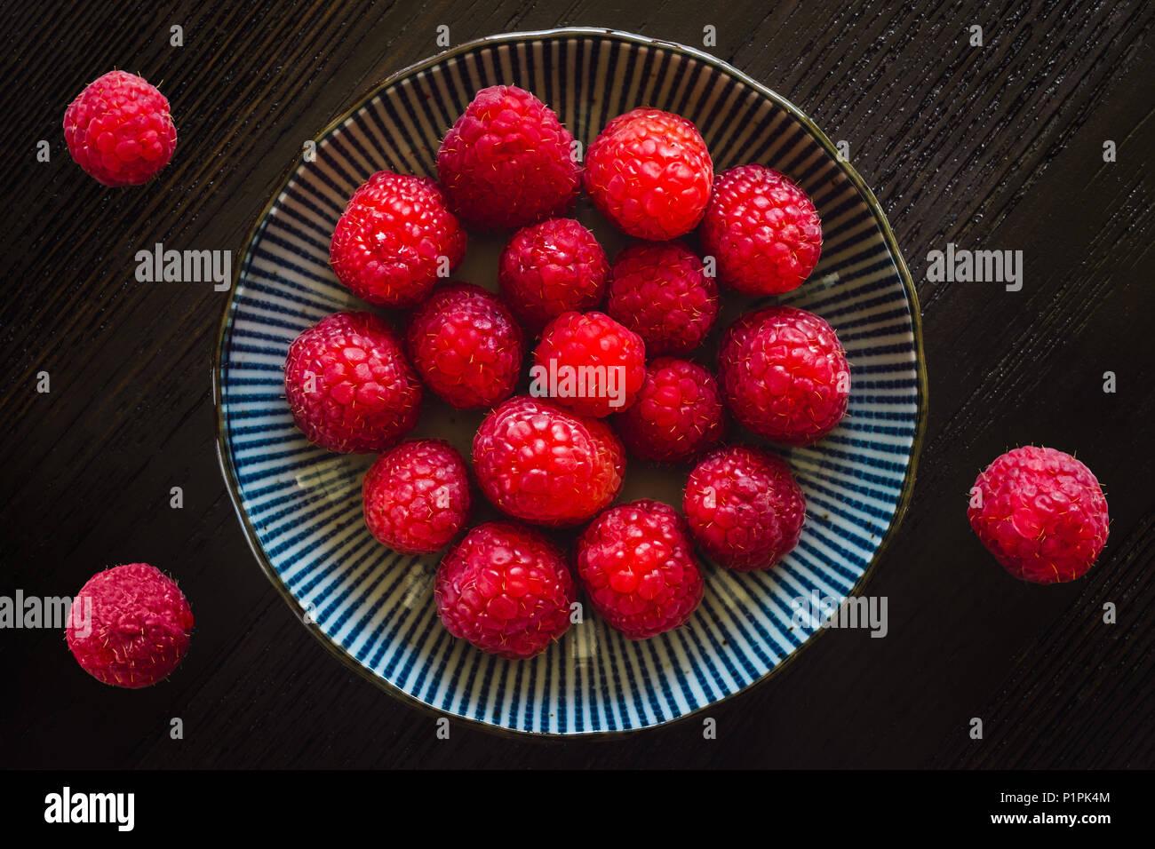 Les framboises dans un bol et sur table en bois sombre. Photo Stock