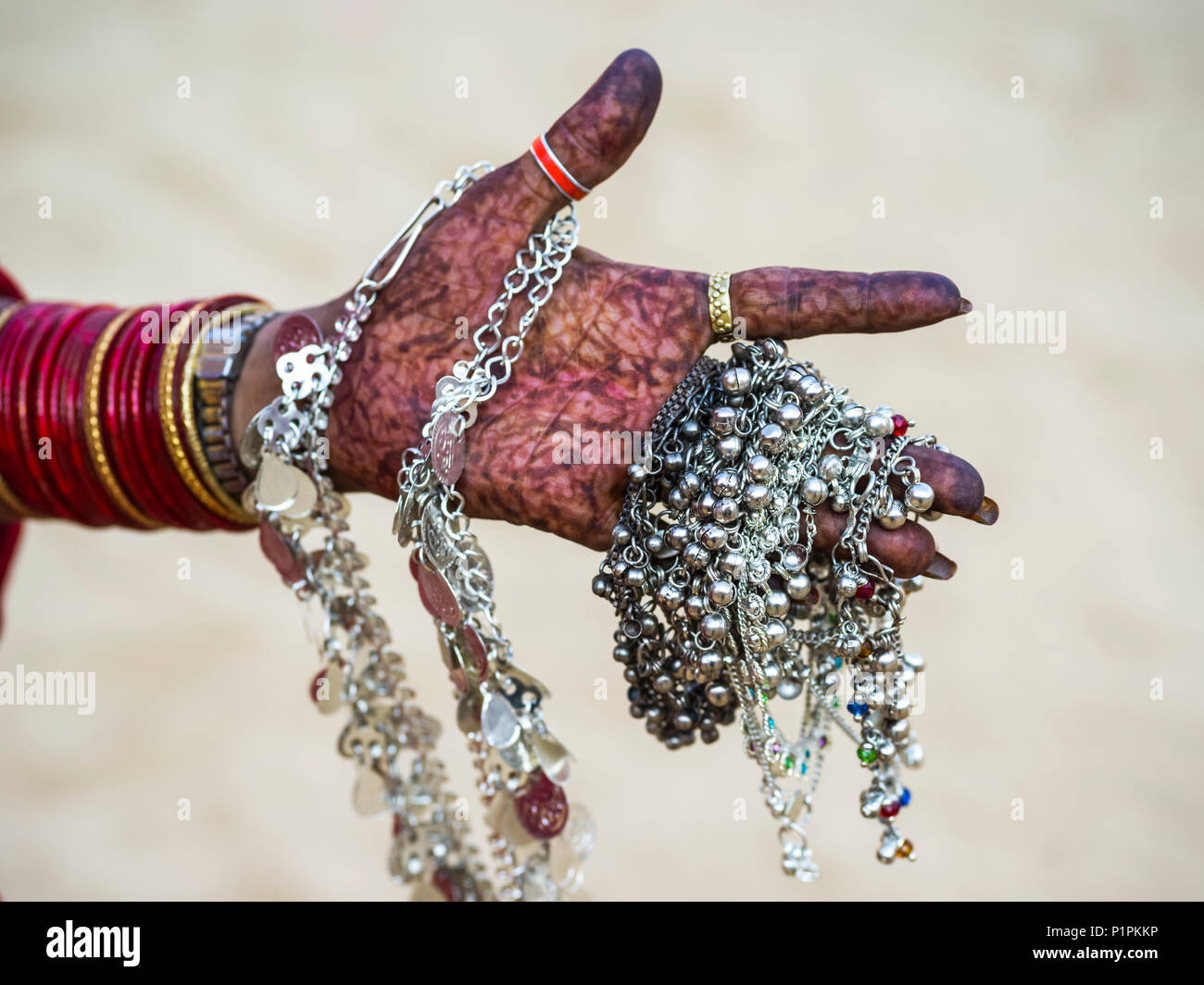 La main d'une femme couverte de henna body art et holding Silver jewelry, Jaisalmer, Rajasthan, India Photo Stock
