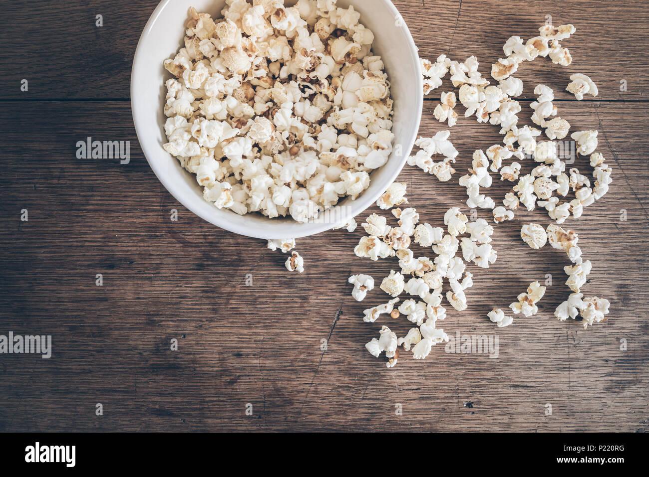 Directement au-dessus de coup de bol rempli de pop-corn et popcorn renversé sur une table en bois rustique Photo Stock