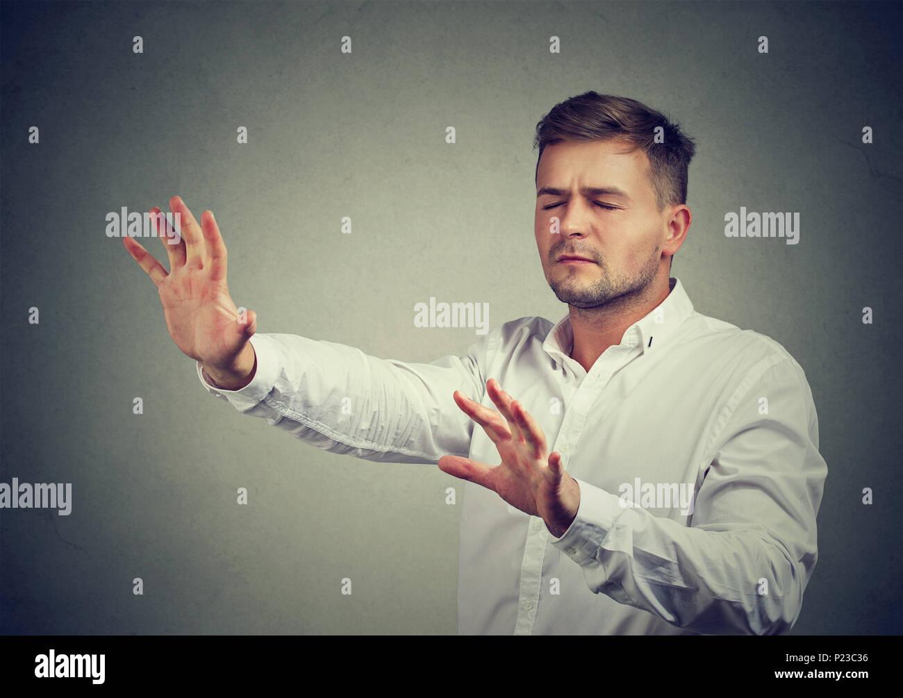 Jeune homme, les yeux fermés la poussée des mains avant de marcher dans l'obscurité avec l'aide de l'intuition. Photo Stock