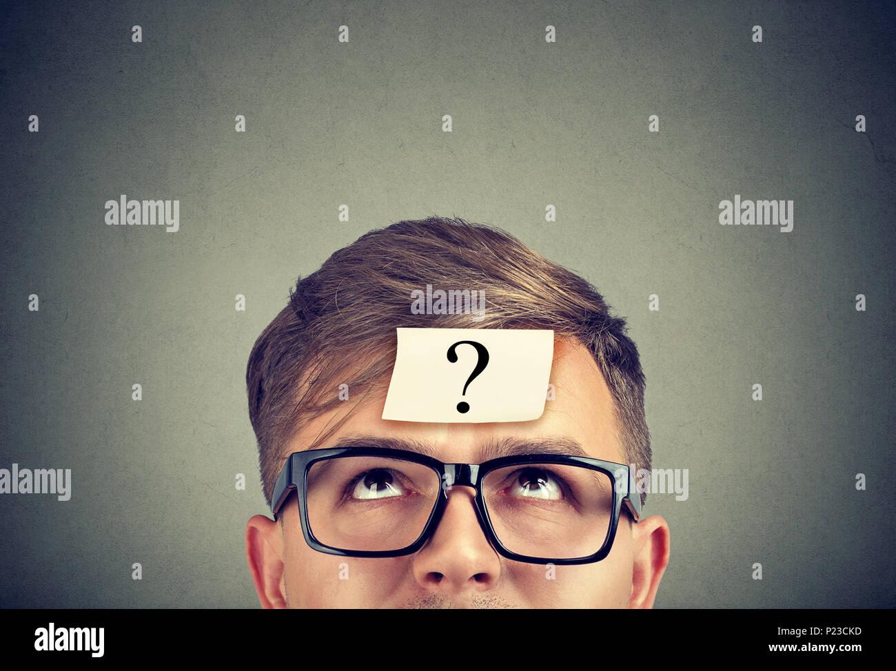 Jeune homme portant des lunettes noires avec un point d'interrogation sur le front à la recherche. Photo Stock
