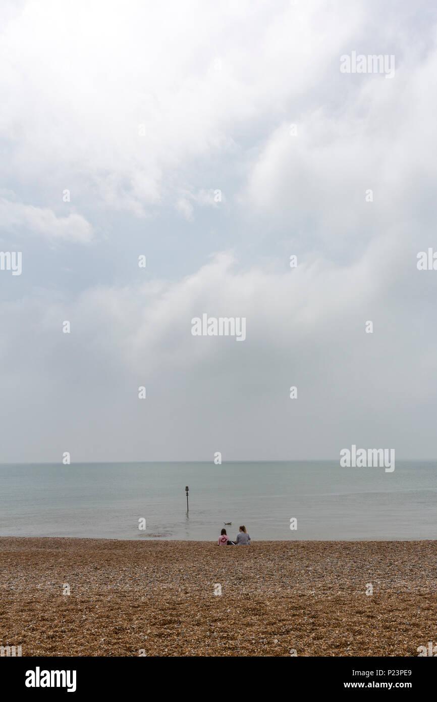Les filles à la recherche de couple isolé de l'horizon à Hastings Beach, Hastings, East Sussex, Angleterre , Royaume-Uni Photo Stock