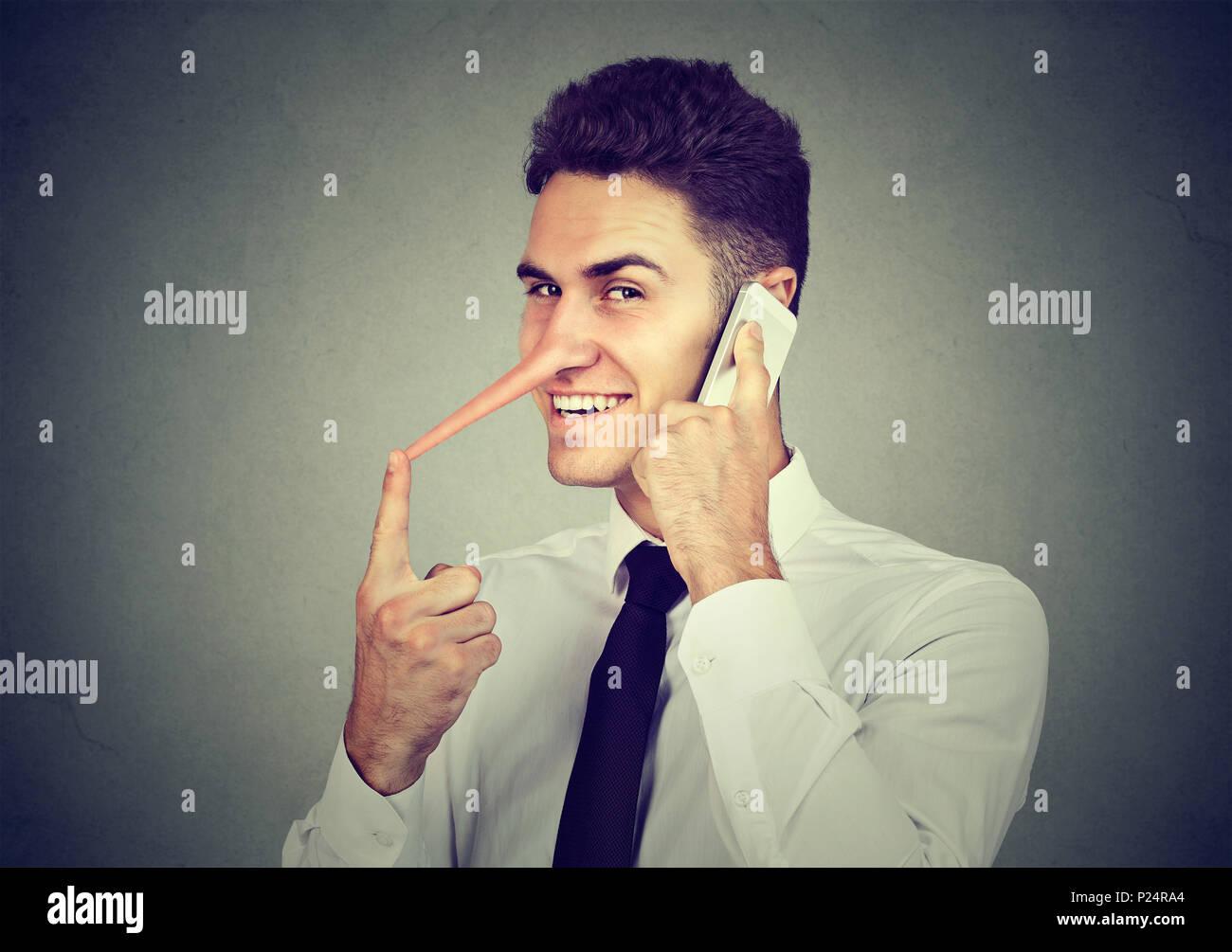 Jeune homme rusé avec long nez talking on mobile phone isolé sur fond de mur gris. Menteur concept. L'émotion des sentiments, de traits de caractère Photo Stock