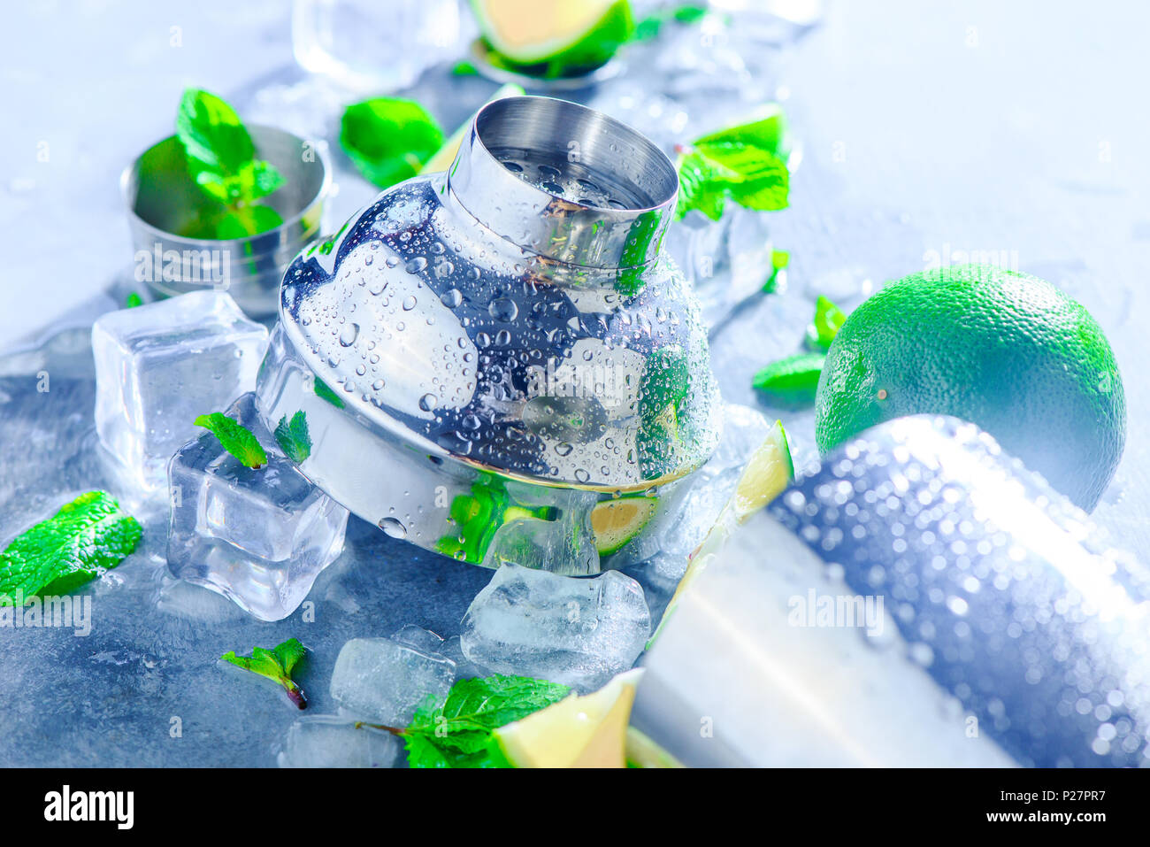 Accessoires bar Shaker et close-up. Mojito cocktail Ingrédients, menthe, citron vert et des glaçons sur un fond noir en gris. Boisson d'été concept avec copie Photo Stock