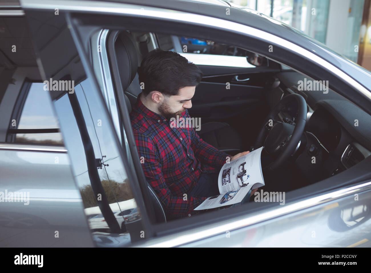 Vendeur à l'intérieur de la voiture brochure lecture Photo Stock