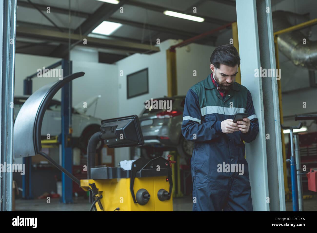 Téléphone mobile à l'aide mécanicien Photo Stock