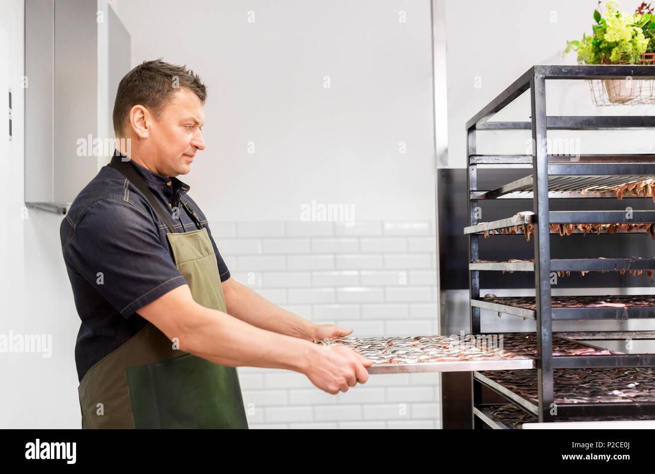 Homme avec bac à fumer le poisson shop ou smokehouse Banque D'Images