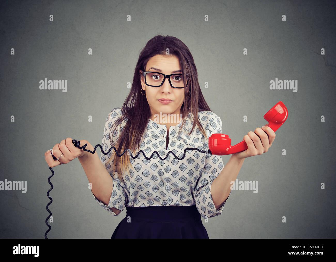 Jeune femme confuse avec de mauvaises nouvelles sur le téléphone Photo Stock