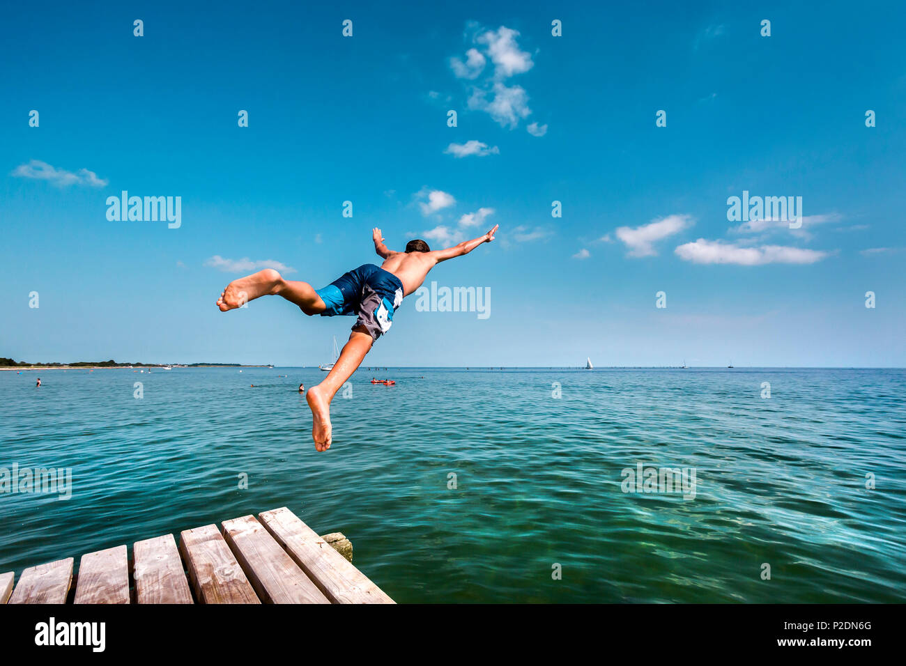 Boy diving à partir d'un quai, South Beach, l'île de Fehmarn Burgtiefe,, côte de la mer Baltique, Schleswig-Holstein, Allemagne Photo Stock