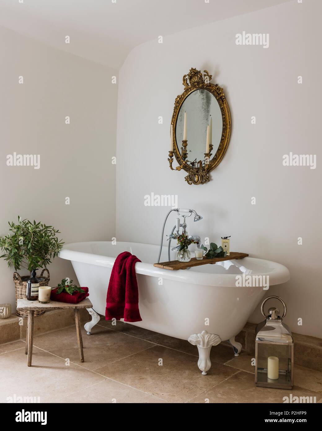Miroir doré antique dans une salle de bains privative avec baignoire ...