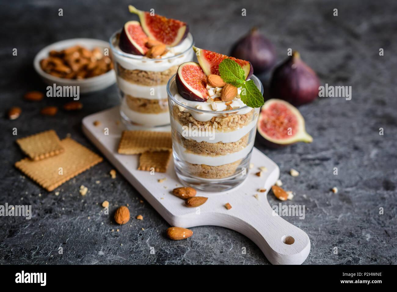Dessert au mascarpone en couches avec des biscuits à la vanille broyées, figues et amandes dans un bocal en verre Photo Stock