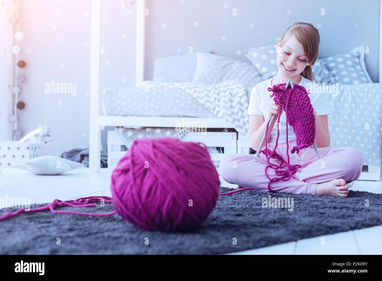 Curieux Smart girl knitting écharpe à la maison Photo Stock