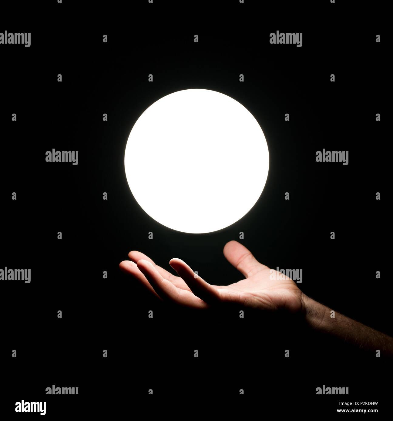 Balle lumineuse sur la main de l'homme isolé sur fond noir Photo Stock
