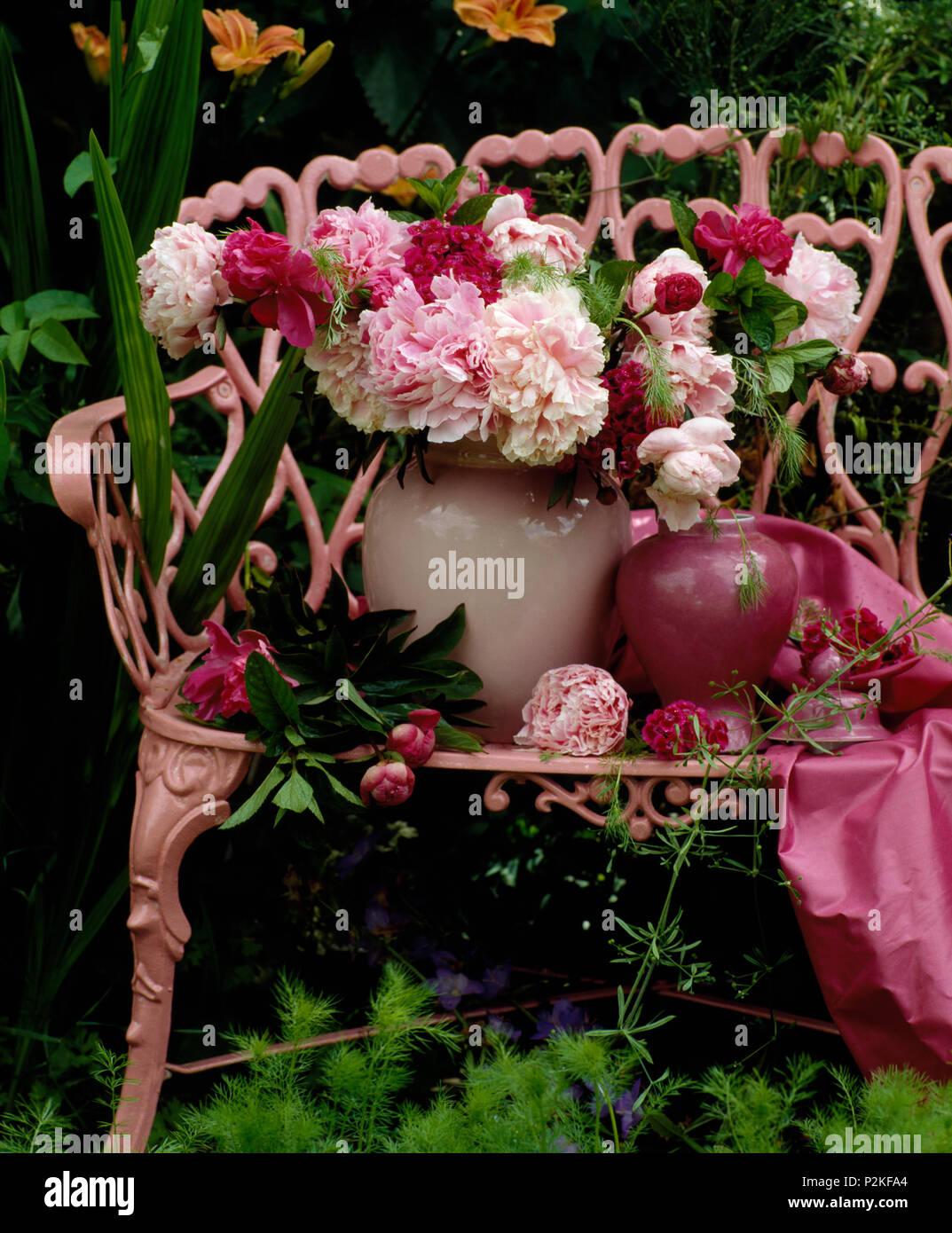 Still-Life de vase de pivoines rose sur banc de jardin peint rose Banque D'Images